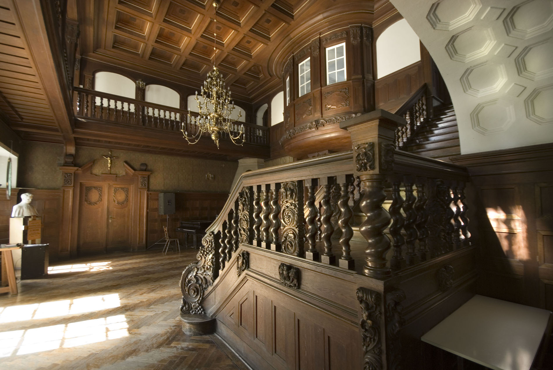 Ozdobna, wyłożona ciemnym drewnem klatka schodowa pałacu