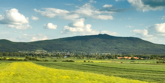Nad zielonymi łakami wznosi się pasmo góry Ślęży, z charakterystycznym szpicem na szczycie