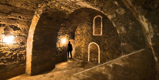 Slwetka człowieka stojącego w przejściu łukowato sklepionej piwnicy